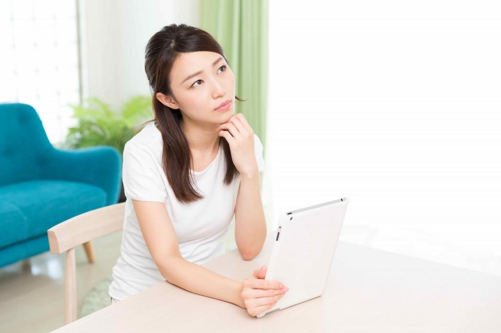 部屋でタブレットを見る女性